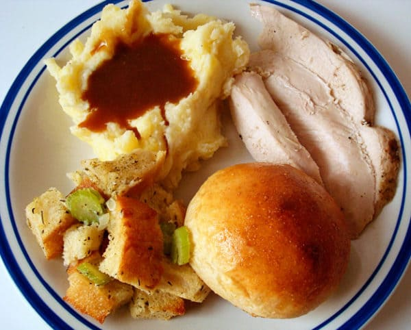 plate full of Thanksgiving stuffing, mashed potatoes and gravy, turkey, and a roll
