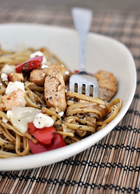 white bowl with cooked pasta, chicken, and red pepper