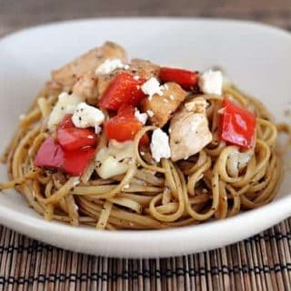 white bowl with cooked spaghetti noodles, chicken pieces, and chopped red pepper