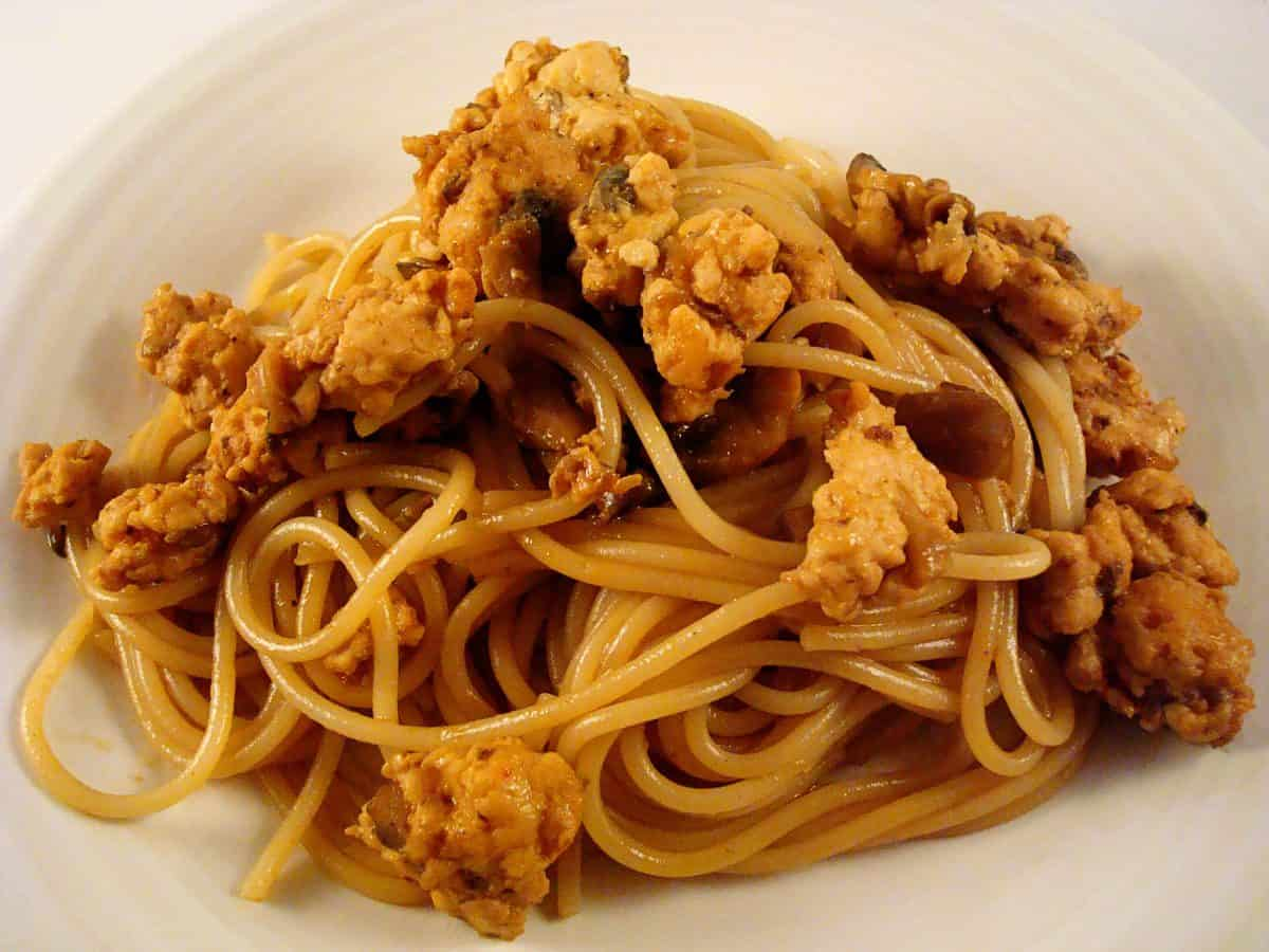 top view of a white plate with cooked spaghetti noodles and meat