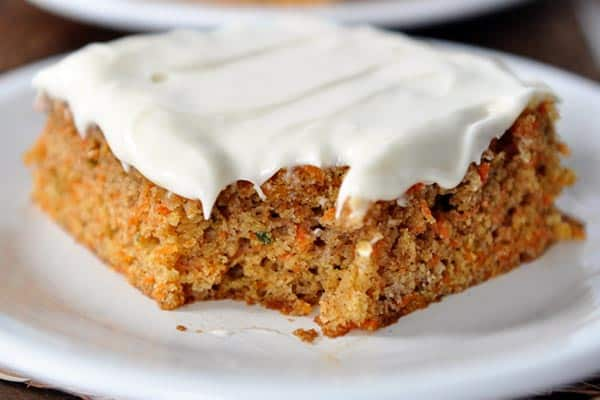 a piece of frosted carrot cake with a bite taken out on a white plate