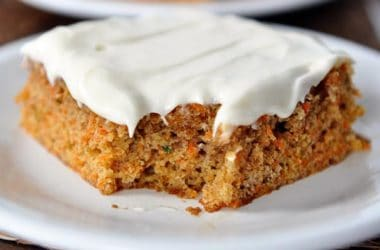piece of carrot cake with whipped white frosting on a white plate
