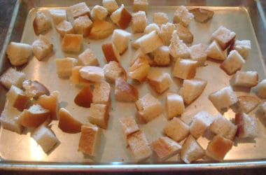 unbaked bread cubes on a cookie sheet