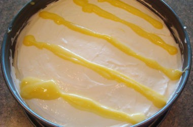 cheesecake in a springform pan with lemon curd stripes on top