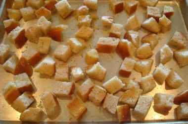 unbaked bread cubes on a metal cookie sheet