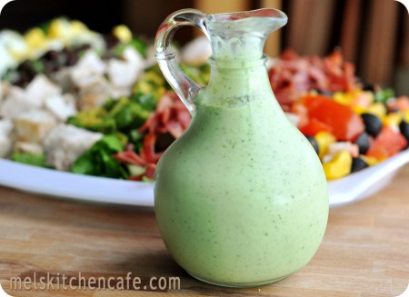 green salad dressing in front of a white plate of salad