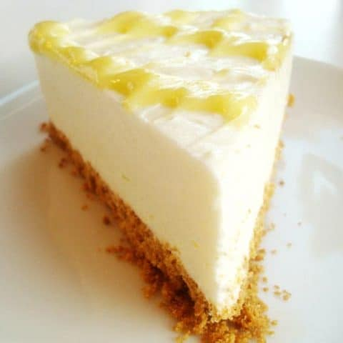 slice of lemon cheesecake with lemon curd drizzle on top on a white plate