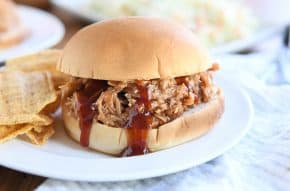 BBQ pork sandwich on bun on white plate