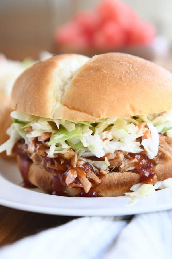 shredded BBQ pork sandwich with coleslaw on white plate