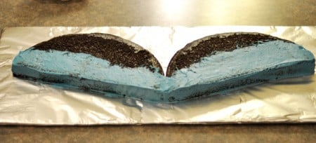 chocolate cake cut in half with the lower half frosted in blue