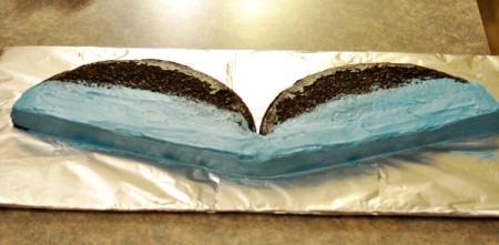 chocolate cake cut in half with the lower half of the cakes frosted in blue