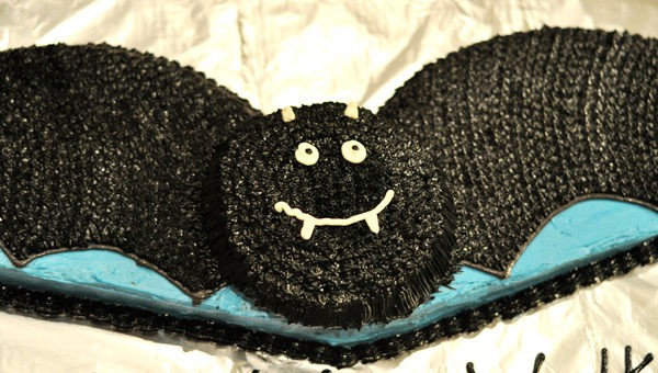 black frosting piped bat cake with a friendly white smile and white eyes