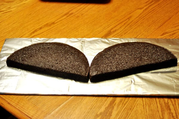 round chocolate cake cut in half put in a bat wing shape on a tinfoil base