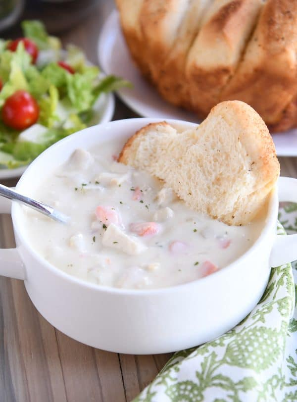 cream cheese chicken vegetable soup with bread in white bowl
