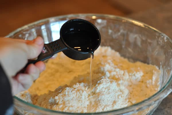 measuring cup adding water to a flour and butter mixture