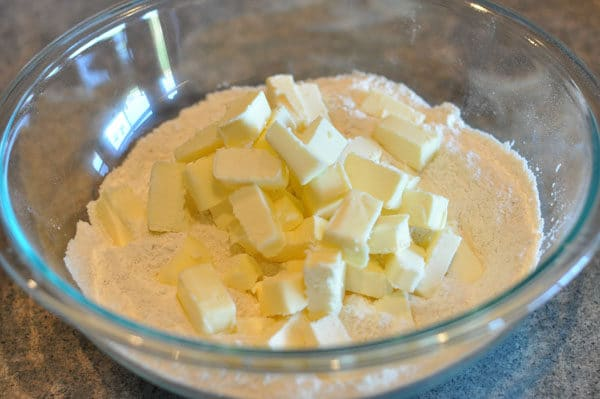 cubed butter on flour in a glass bowl