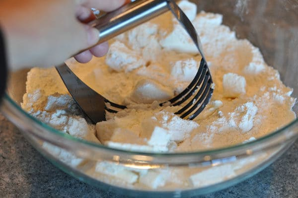 pastry blender blending cubed butter and flour in a glass bowl