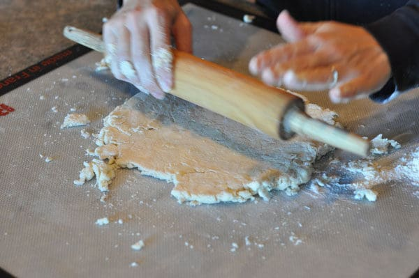 pie crust being rolled out with a rolling pin