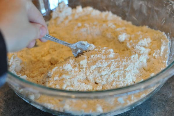 fork mixing water and dough mixture together in a glass bowl