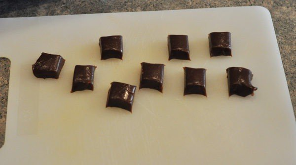 small squares of chocolate caramels on a white cutting board