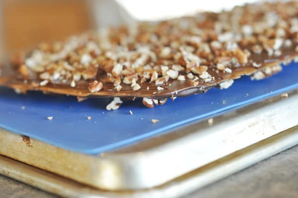 toffee buttercrunch toffee on a blue liner on top of a cookie sheet