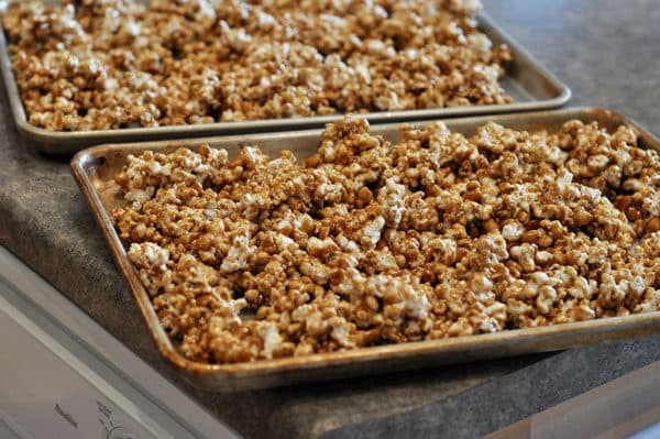 two cookie sheets full of toffee coated popcorn