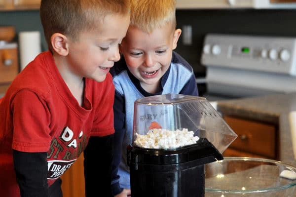 two little boys looking happily at popcorn popping in a popcorn maker