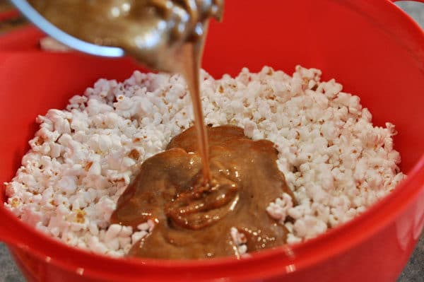 caramel mixture being poured over a red bowl of popped popcorn