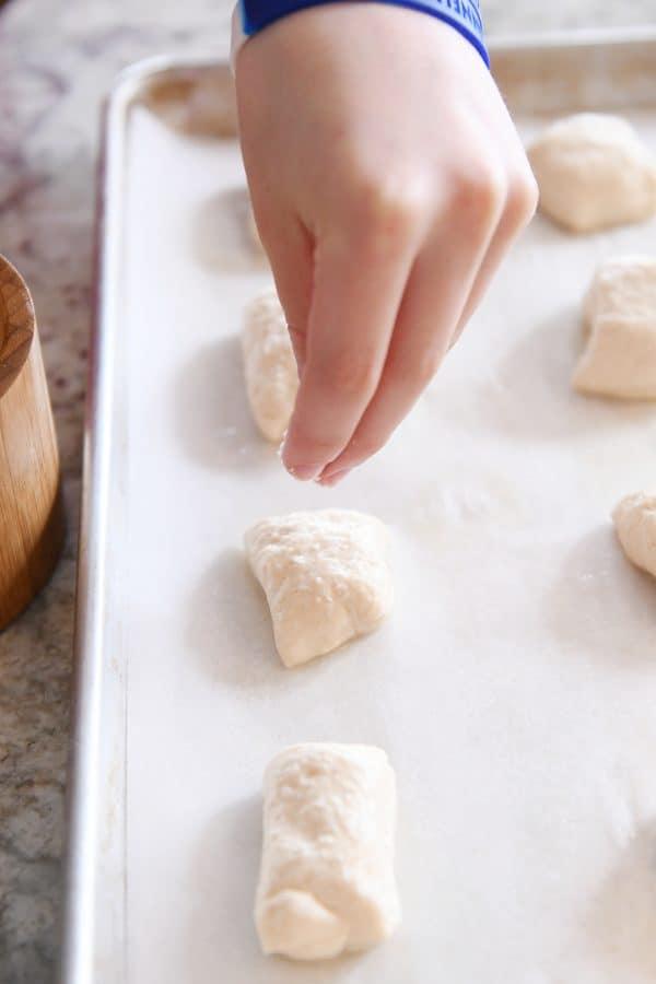 sprinkling easy homemade soft pretzel bites with salt before baking