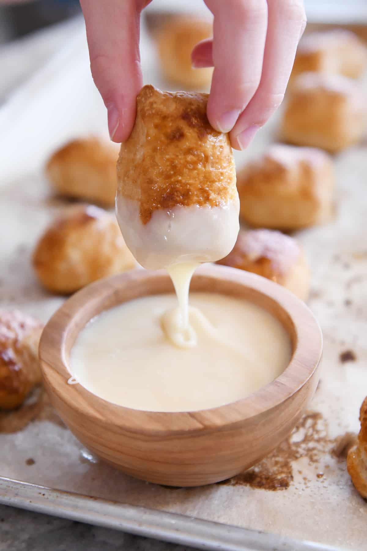 dipping easy homemade soft pretzel bites in homemade cheese sauce