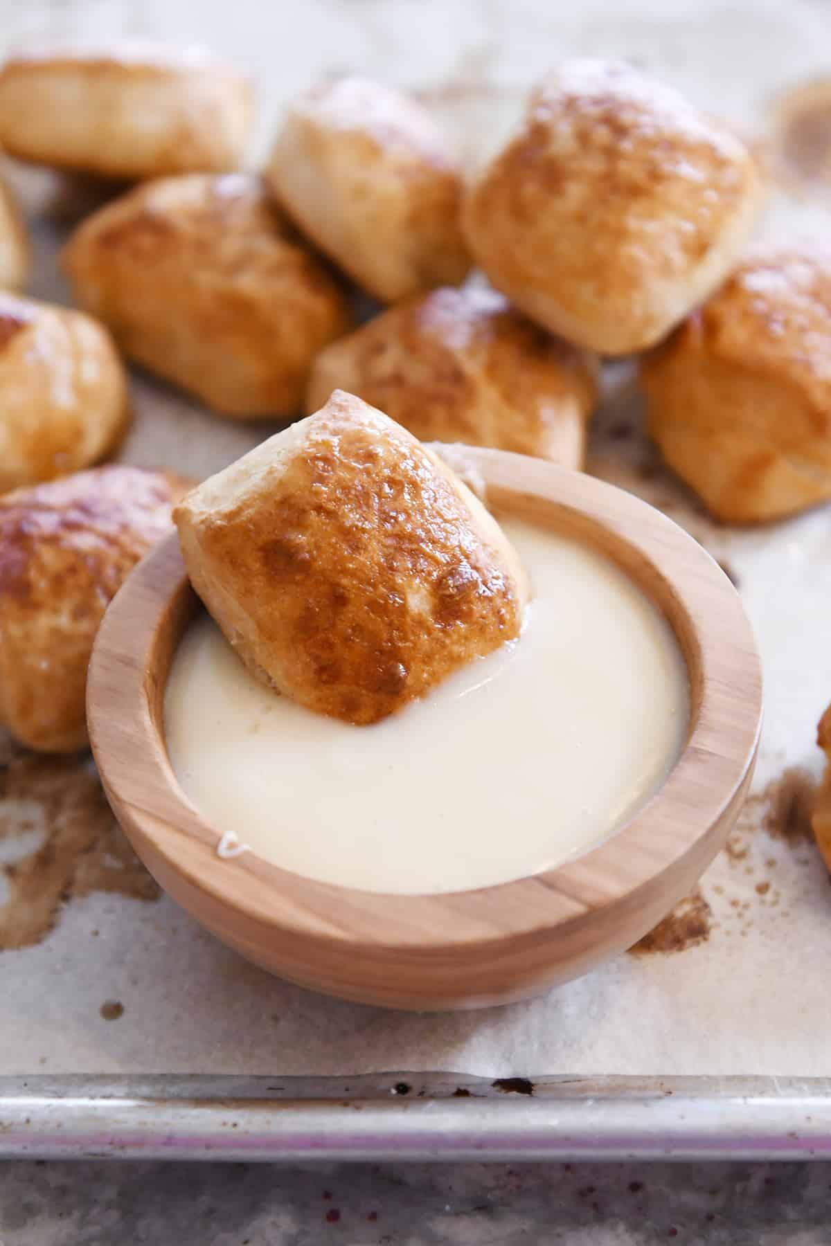 soft pretzel bite sitting in bowl of warm cheese sauce