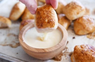 dipping easy homemade soft pretzel bites in homemade cheese sauce
