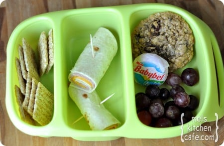 top view of a green divided lunch tray with crackers, ham cheese roll, grapes, Babybel, and cookie