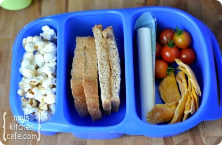 top view of a blue divided lunch box with popcorn, sandwich, cheese stick, tomatoes, and chips