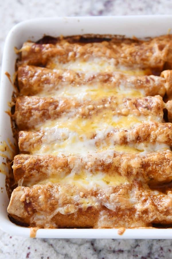 Baked pan of red sauce chicken enchiladas with lots of crusty cheese on top.