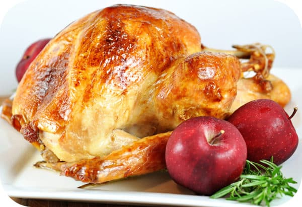 baked turkey with full apples on a white platter
