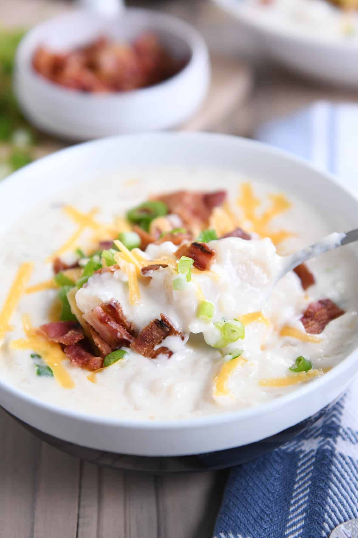 spoon taking scoop out of loaded baked potato soup in white bowl