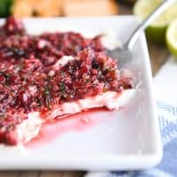 white dish with softened cream cheese topped with chopped cranberry jalapeno mixture