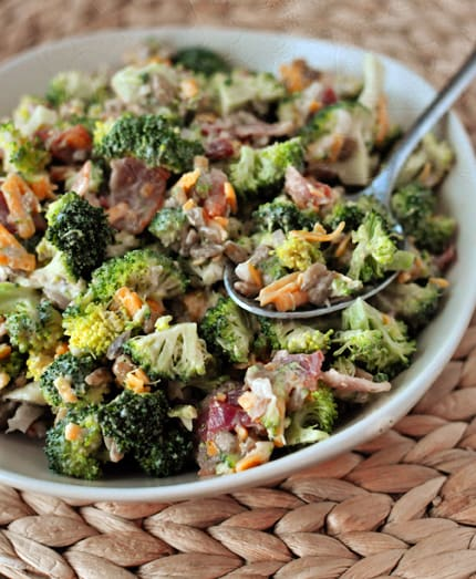 Full bowl of homemade broccoli salad with a spoonful of it on top ready to eat.