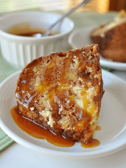 a piece of caramel drizzled apple bundt cake on a white plate