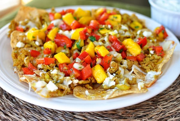 white plate full of nachos with mango salsa on top