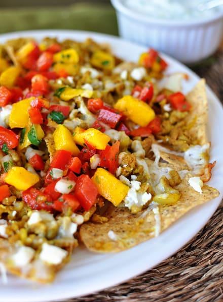 white plate full of mango and tomato-topped nachos