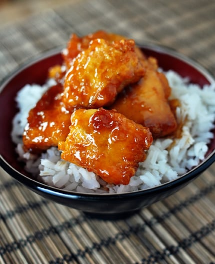 bowl with white rice topped with big pieces of sticky red sauce chicken