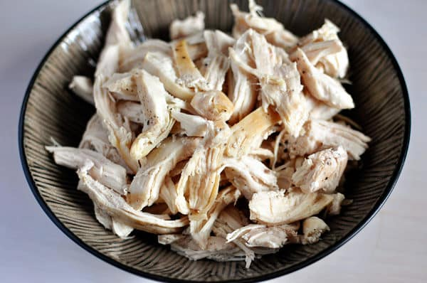 Cooked shredded, salted and peppered chicken, in a large ceramic bowl.