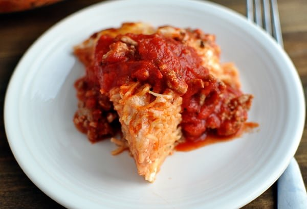 a triangle shaped serving of cooked spaghetti pie topped with red spaghetti sauce