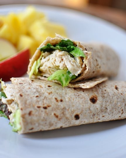 a chicken caesar salad wrap cut in half on a white plate with fruit on the background