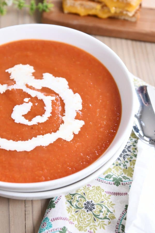 the best classic tomato soup in white bowl with swirl of heavy cream