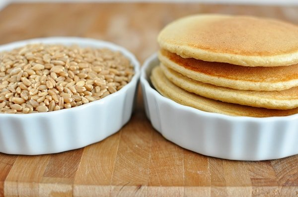 two white ramekins with one filled with wheat berries and the other with stacked pancakes