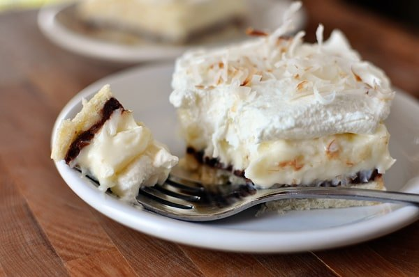 a layered coconut cream pie bar with a bite taken out on a white plate