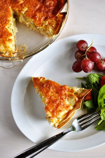 a slice of cheesy quesadilla pie on a white plate next to a cluster of grapes and green salad